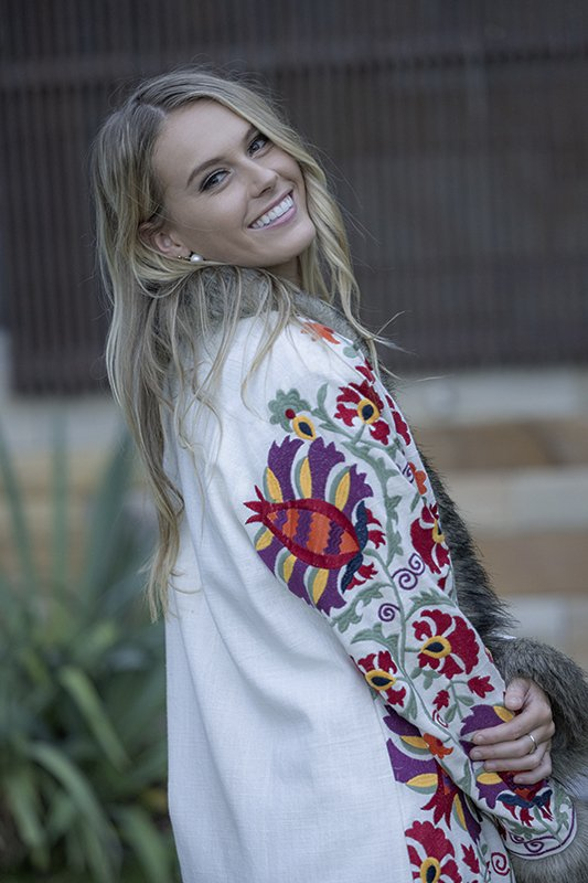 Gorgeous, embroidered Boho Coat with faux fur trim from Cienna Designs. The most fabulous Coat Ever! Stunning multi coloured embroidery over a off-white base, the front trimmed with faux fair trimming. Ties with pom poms in the middle.