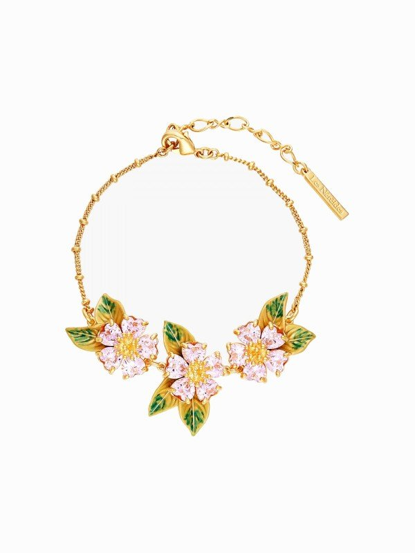 A thin bracelet from the Hanami collection, Heart Flowers, it is composed of three flowers with heart-shaped faceted petals on green foliage, hand-painted using the enamelling technique of La Maison Les Néréides.