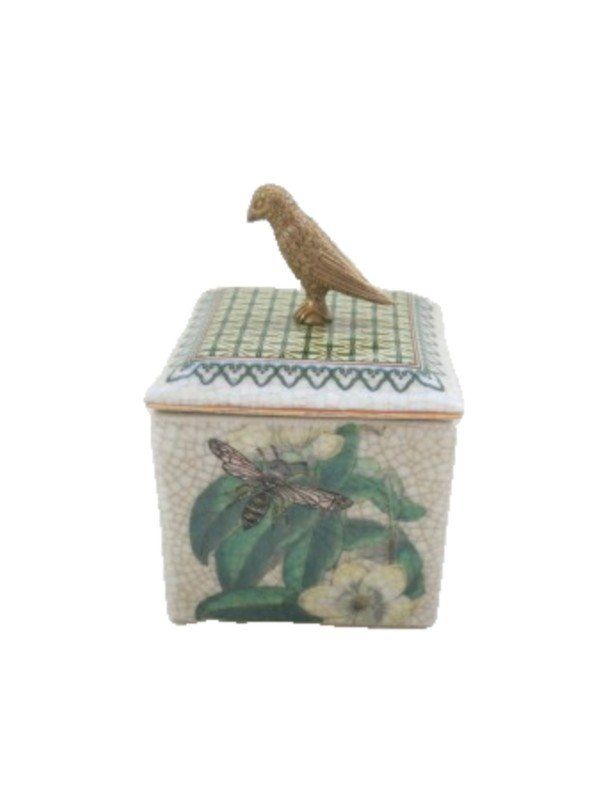 Square 9 x 9cm trinket box with brass bird on top to service as a handle. Porcelain body with crackle style glaze and palm tree bee pattern in the artwork.