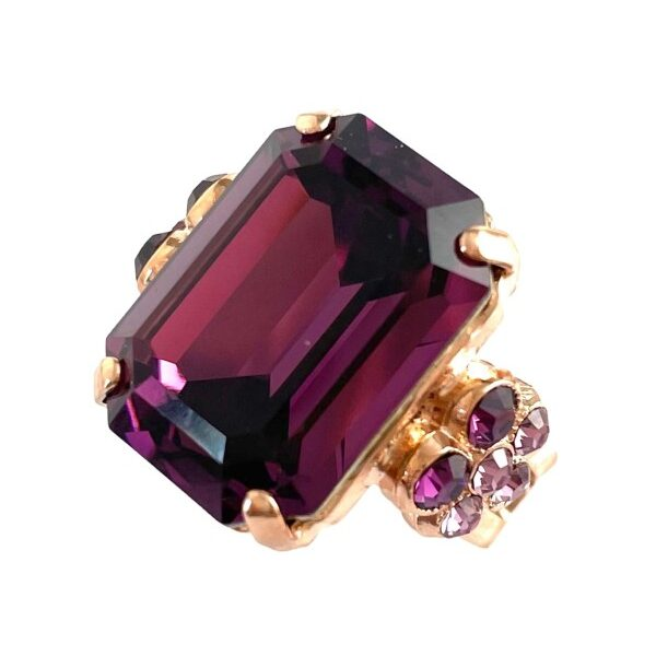 Exquisite port wine purple crystal cut as a rectangle, features as the centrepiece of this ring. Mariana has a flower setting on either side trimmed in mauve and violet crystals. Adjustable band, rose gold plating.