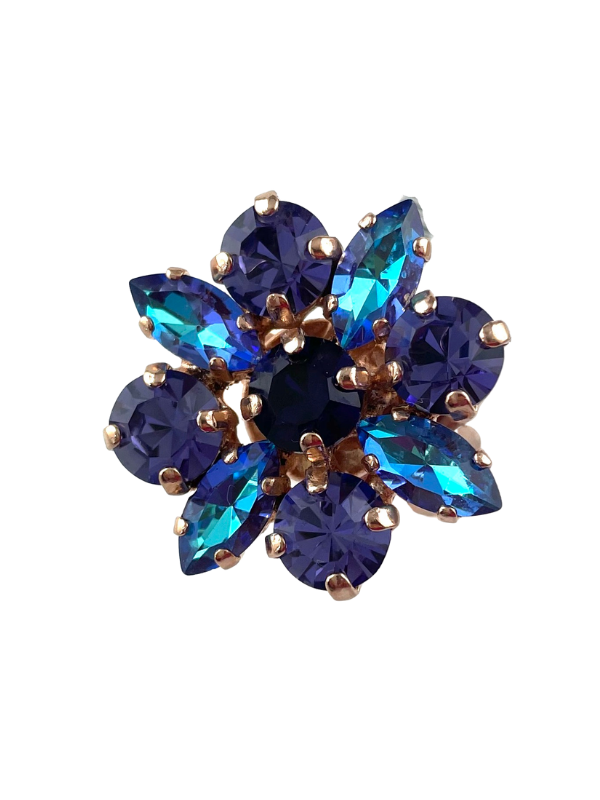 As enticing as a daisy on a mountainside, this flower dress ring features violet and stormy blue crystals set as a flower. Adjustable band with rose gold plating.