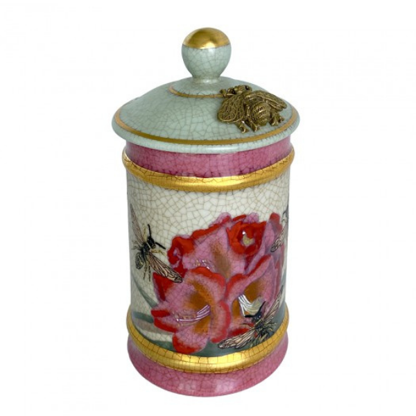A decorative, lidded jar from Creatively Active Minds. Porcelain designed with crackle glaze and pink and red tropical lily artwork. Trimmed with gold highlights and a brass bee on the lid.